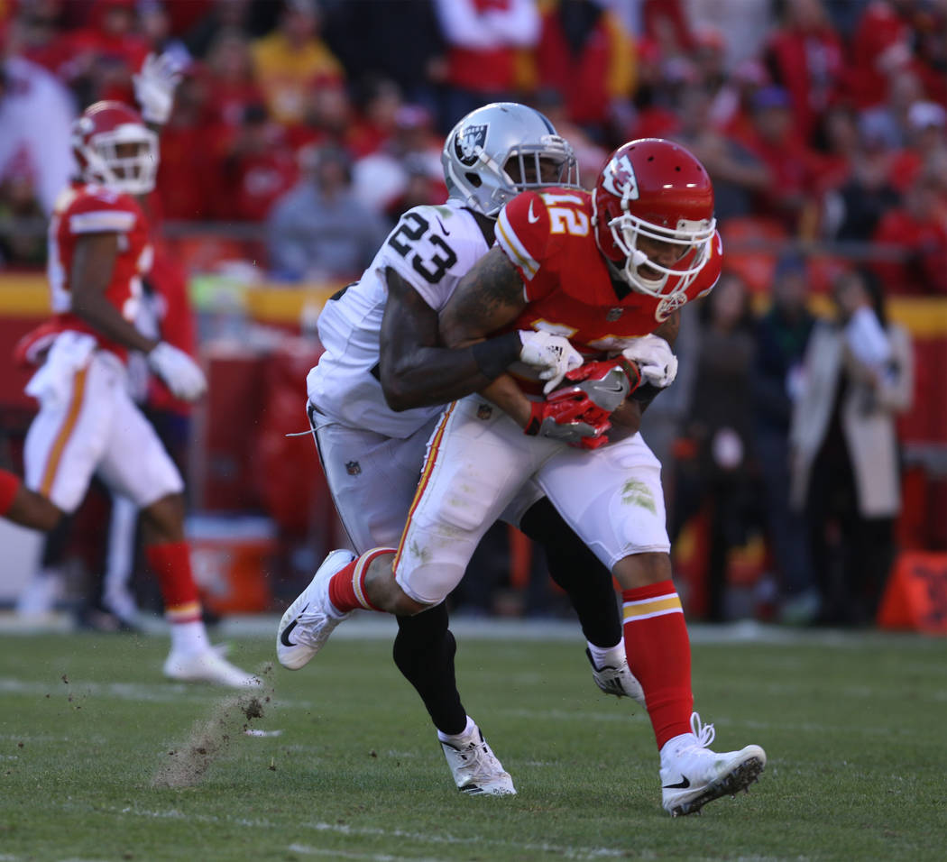 Kansas City Chiefs wide receiver Albert Wilson (12) holds on to a catch as Oakland Raiders cornerback Dexter McDonald (23) tries to tackle him during the first half of a NFL game in Kansas City, M ...