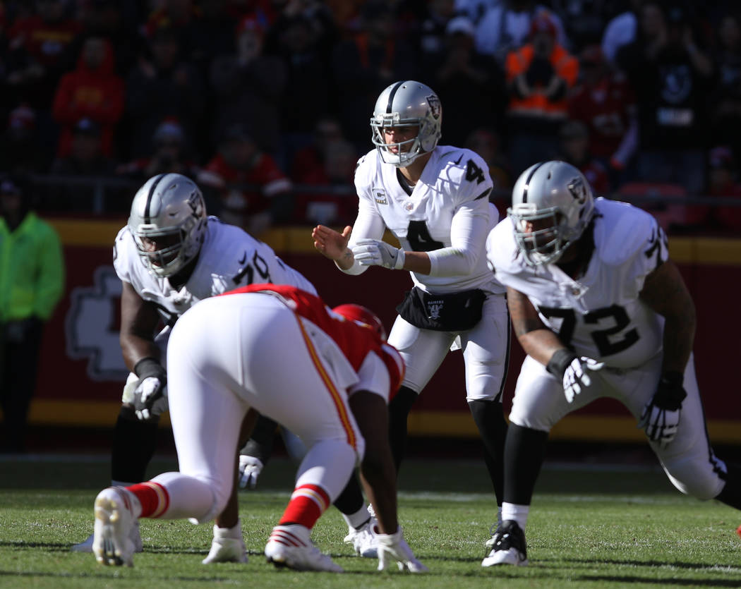 Oakland Raiders quarterback Derek Carr (4) on the line of scrimmage during the first half of a NFL game against the Kansas City Chiefs in Kansas City, Mo., Sunday, Dec. 10, 2017. Heidi Fang Las Ve ...