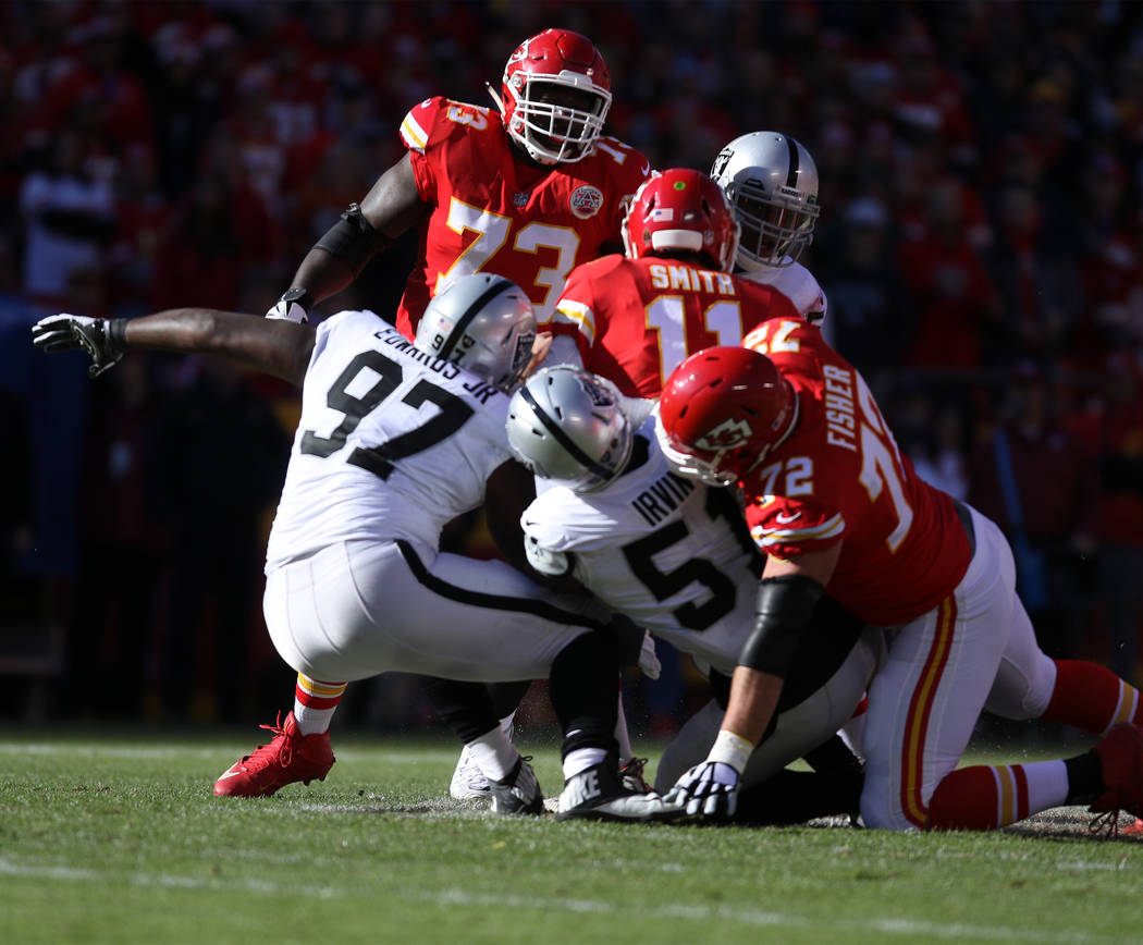 Oakland Raiders outside linebacker Bruce Irvin (51) sacks Kansas City Chiefs quarterback Alex Smith (11) with the help of defensive end Mario Edwards (97) as offensive tackle Eric Fisher (72) and  ...