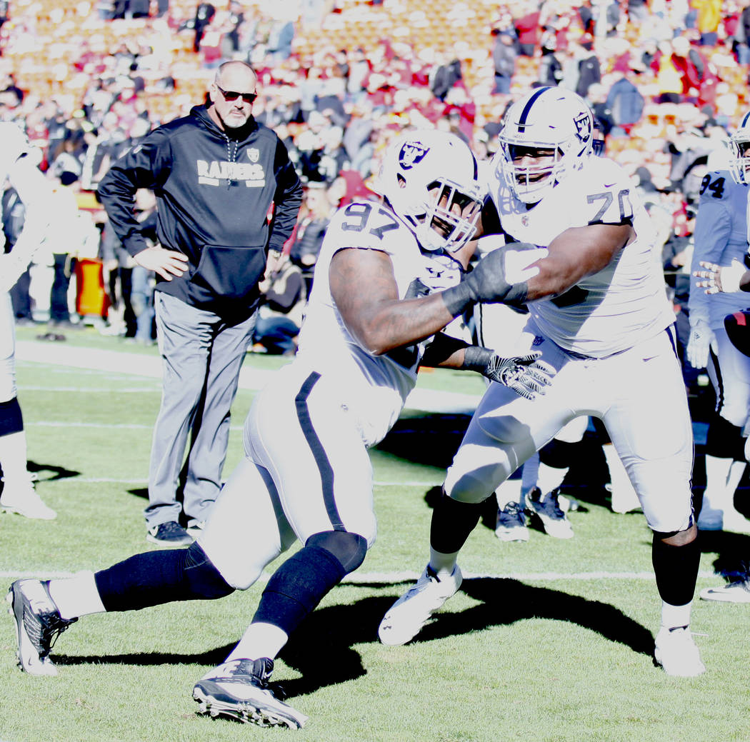 Oakland Raiders offensive guard Kelechi Osemele (70) and Oakland Raiders defensive end Mario Edwards (97) go through drills prior to their NFL game against the Kansas City Chiefs in Kansas City, M ...
