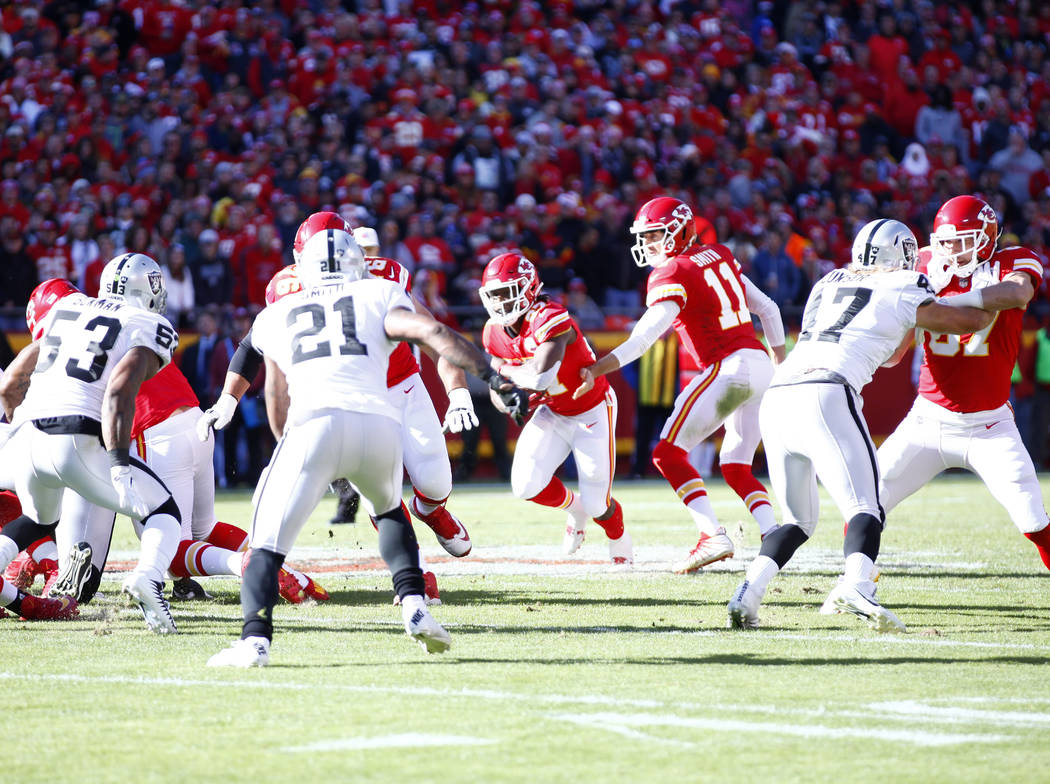 Kansas City Chiefs quarterback Alex Smith (11) hands off to running back Kareem Hunt (27) during the first half of a NFL game against the Oakland Raiders in Kansas City, Mo., Sunday, Dec. 10, 2017 ...