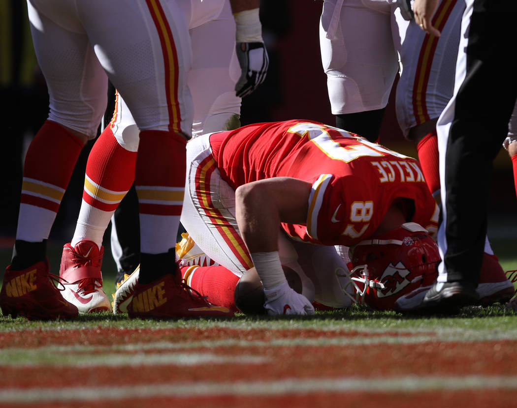 Kansas City Chiefs tight end Travis Kelce (87) is briefly shook up after catching a pass near the end zone during the first half of a NFL game against the Oakland Raiders in Kansas City, Mo., Sund ...