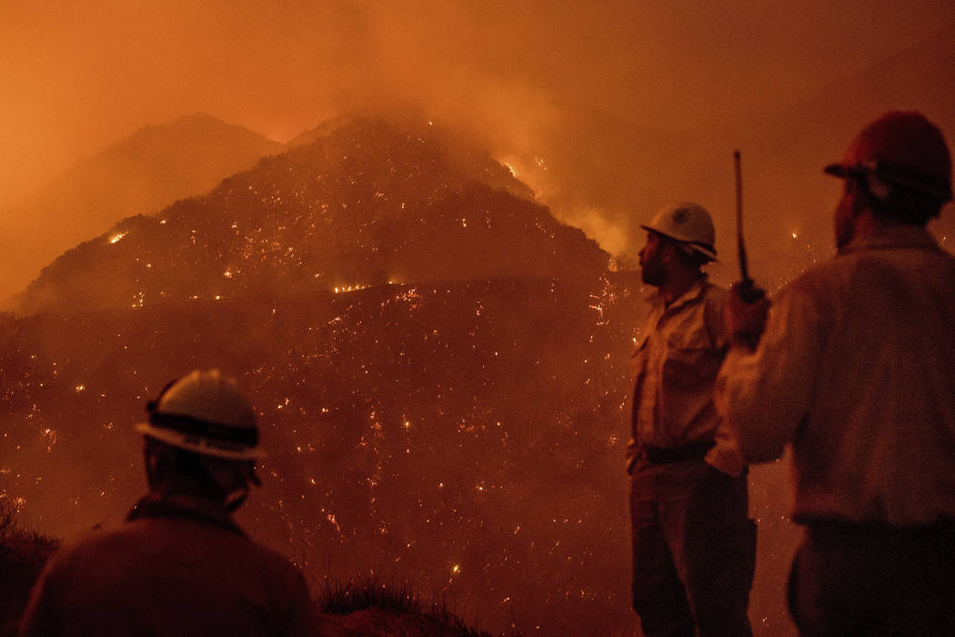 Firefighters monitor the Thomas fire as it burns through Los Padres National Forest near Ojai, Calif., on Friday, Dec. 8, 2017. (Noah Berger/AP Photo)