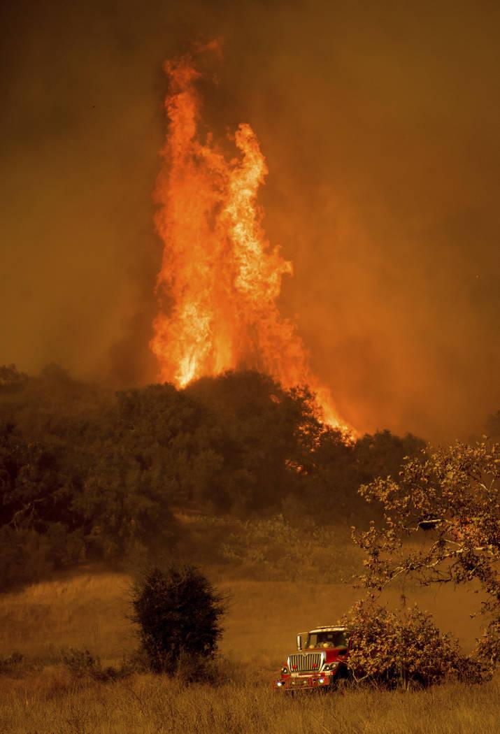 A fire engine passes flames as a wildfire burns along Santa Ana Road near Ventura, Calif., on Saturday, Dec. 9, 2017. (Noah Berger/AP Photo)