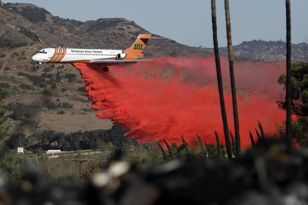 A plane drops fire retardant on a wildfire Friday, Dec. 8, 2017, in Fallbrook, Calif. The wind-swept blazes have forced tens of thousands of evacuations and destroyed dozens of homes in Southern C ...