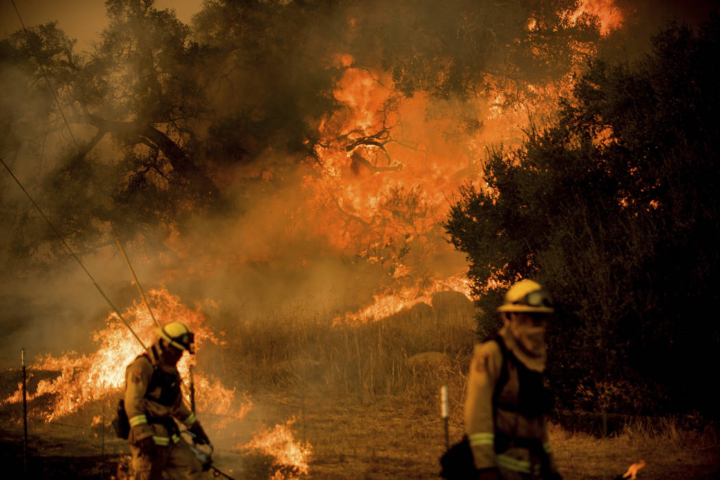 Firefighters light backfire while trying to keep a wildfire from jumping Santa Ana Rd. near Ventura, Calif., on Saturday, Dec. 9, 2017. (Noah Berger/AP Photo)