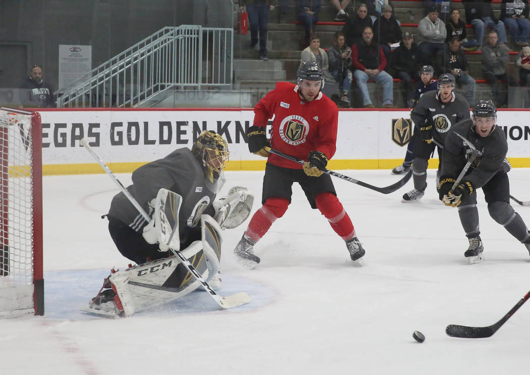 Vegas Golden Knights goalie Marc-Andre Fleury and forward William Carrier, center, keep their eye on the puck during team's practice on Monday, Dec. 11, 2017, in Las Vegas. Bizuayehu Tesfaye Las V ...