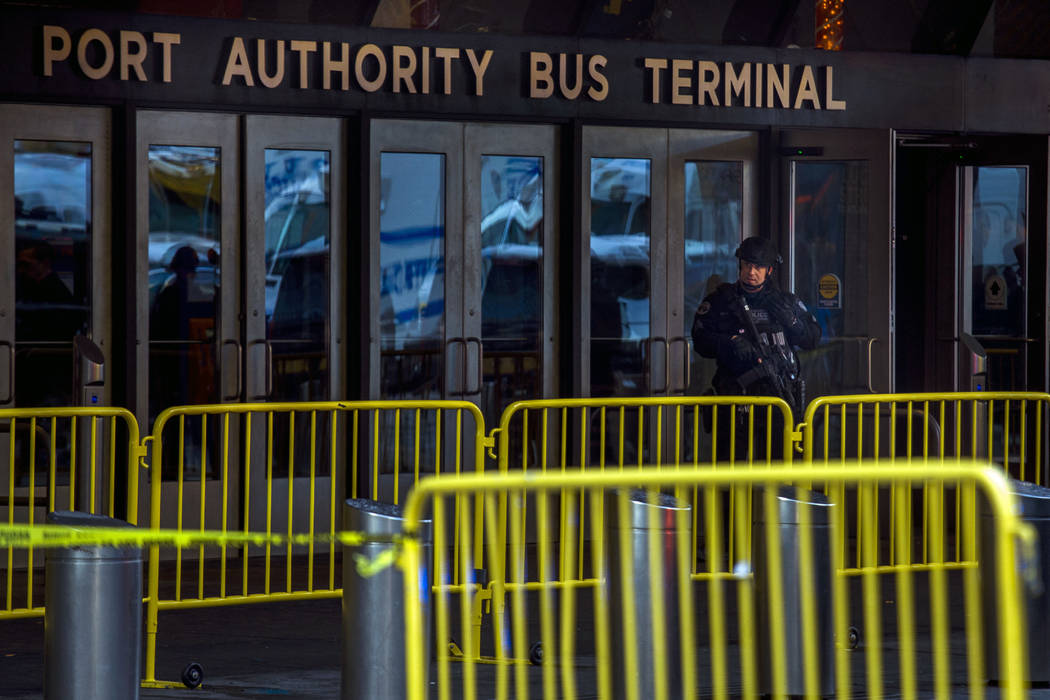 A police officer stands guard in front of Port Authority Bus Terminal as law enforcement respond to a report of an explosion near Times Square on Monday, Dec. 11, 2017, in New York. (Andres Kudack ...