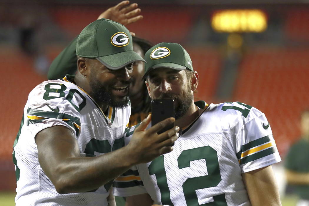 Green Bay Packers tight end Martellus Bennett (80) and quarterback Aaron Rodgers (12) look at Bennett's phone after an NFL preseason football game against the Washington Redskins in Landover, Md., ...