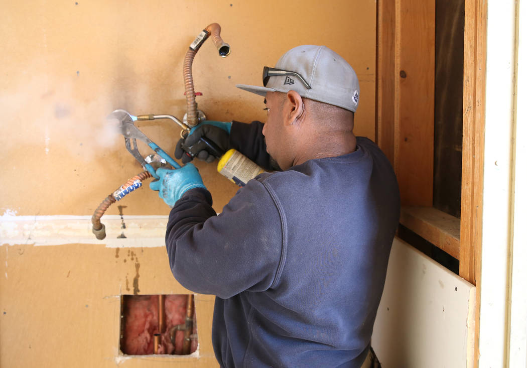 Abraham Gonzalez uses handheld propane torch to remove old pipes from the Las Vegas home of 87-year-old U.S. Air Force veteran Louise Jones Tuesday, Dec. 12, 2017. Rebuilding Together, a nationwid ...