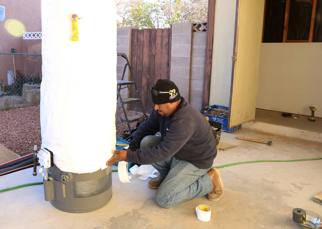 Abraham Gonzalez insulates a water heater outside the Las Vegas home of 87-year-old U.S. Air Force veteran Louise Jones Tuesday, Dec. 12, 2017. Rebuilding Together, a nationwide non-profit organiz ...