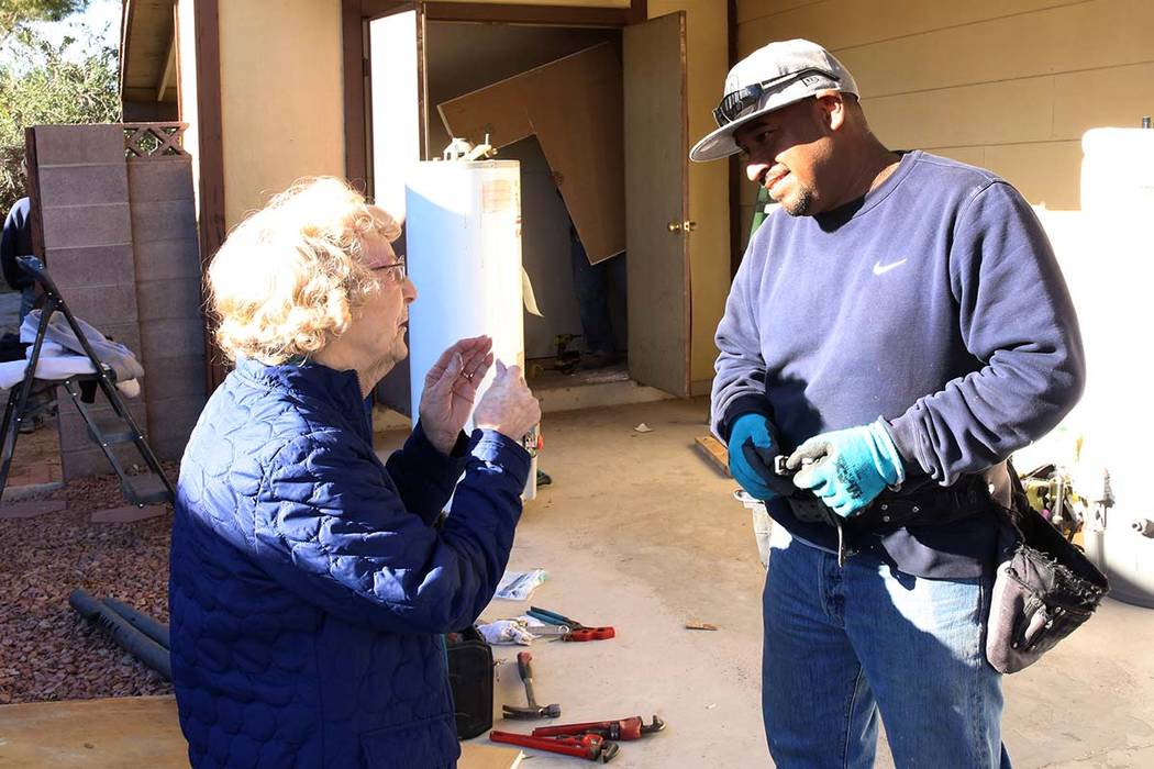 Louise Jones, 87-year-old U.S. Air Force veteran, chats with Abraham Gonzalez outside her Las Vegas home Tuesday, Dec. 12, 2017. Rebuilding Together, a nationwide non-profit organization, coordina ...