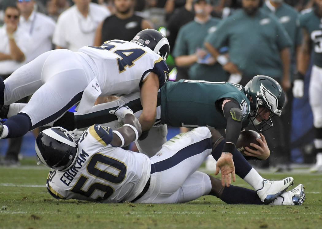 Philadelphia Eagles quarterback Carson Wentz, right, is tackled by Los Angeles Rams linebacker Samson Ebukam (50) and inside linebacker Bryce Hager during the second half of an NFL football game S ...