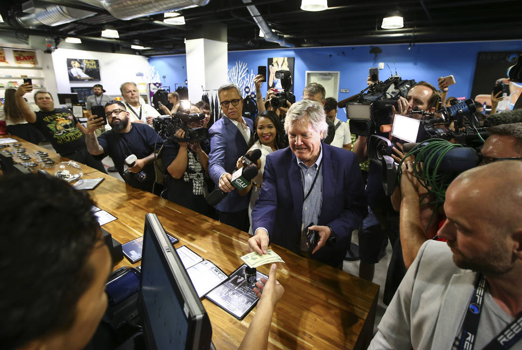 Sen. Tick Segerblom, D-Las Vegas, hands over cash to be the first customer to buy recreational marijuana at Reef Dispensaries in Las Vegas on Saturday, July 1, 2017. Chase Stevens Las Vegas Review ...