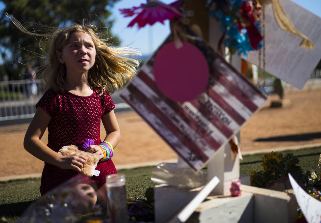 Seven-year-old Brooke Patterson of Lomita, Calif. visits a makeshift memorial for her mother, Lisa Patterson, who was one of 58 people who died in the Oct. 1 shooting at a music festival, near the ...