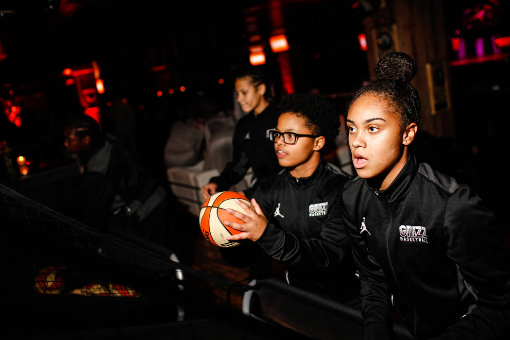 Spring Valley High School girls basketball team's Deja McDonald, 15, left, and Kiana Turenne, 15, right, shoot basketballs before the start of the reveal of the Las Vegas Aces WNBA basketball team ...