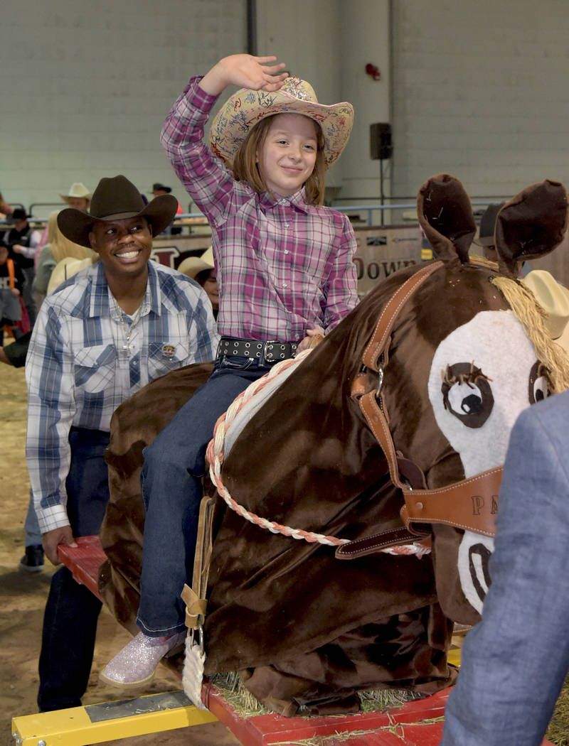 Nadia Wiggins makes his 8 seconds on her bareback ride as special needs children experience the world of rodeo with Wrangler NFR contestants, announcers, personnel and even Miss Rodeo America at T ...
