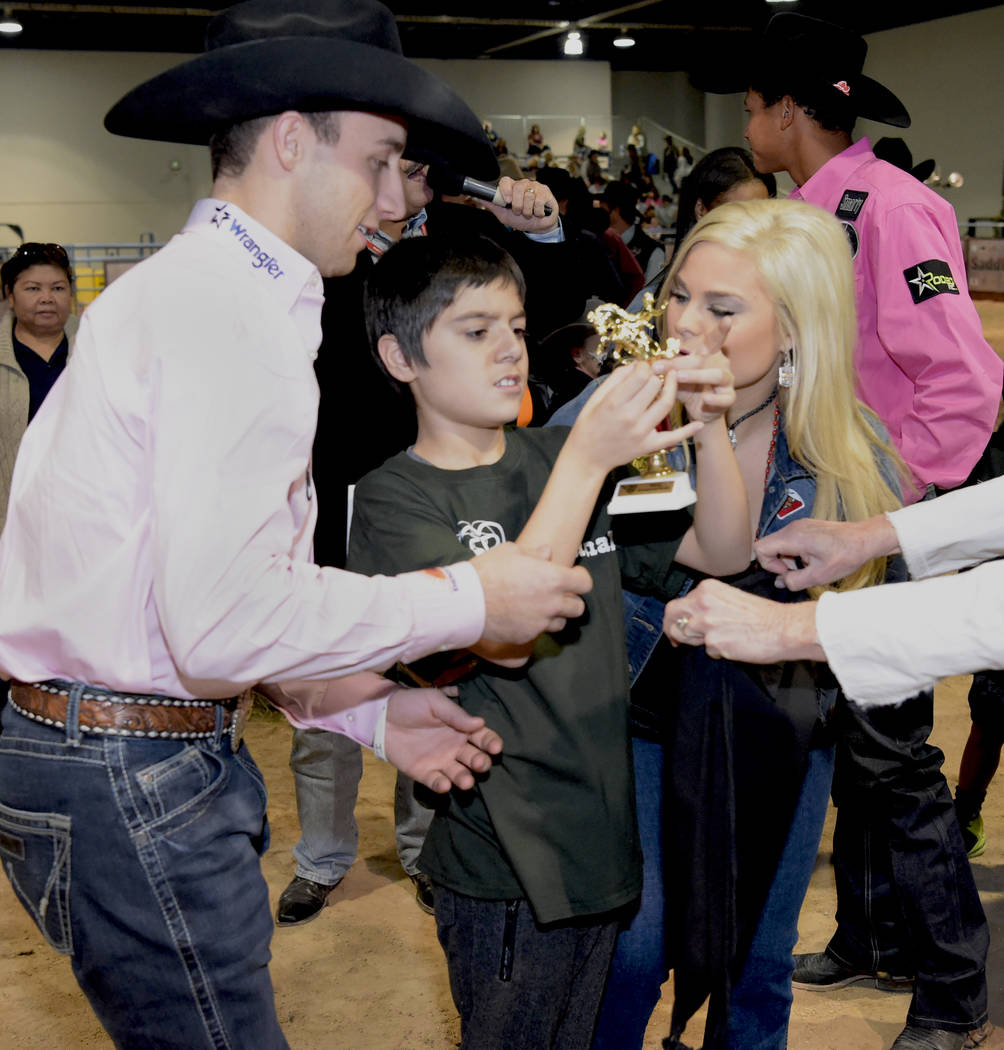 Eric Sanchez, center, is presented his trophy by 2017 CBR World Champion Sage Kimzey, left, and Alexis Bloomer as special needs children experience the world of rodeo with Wrangler NFR contestants ...