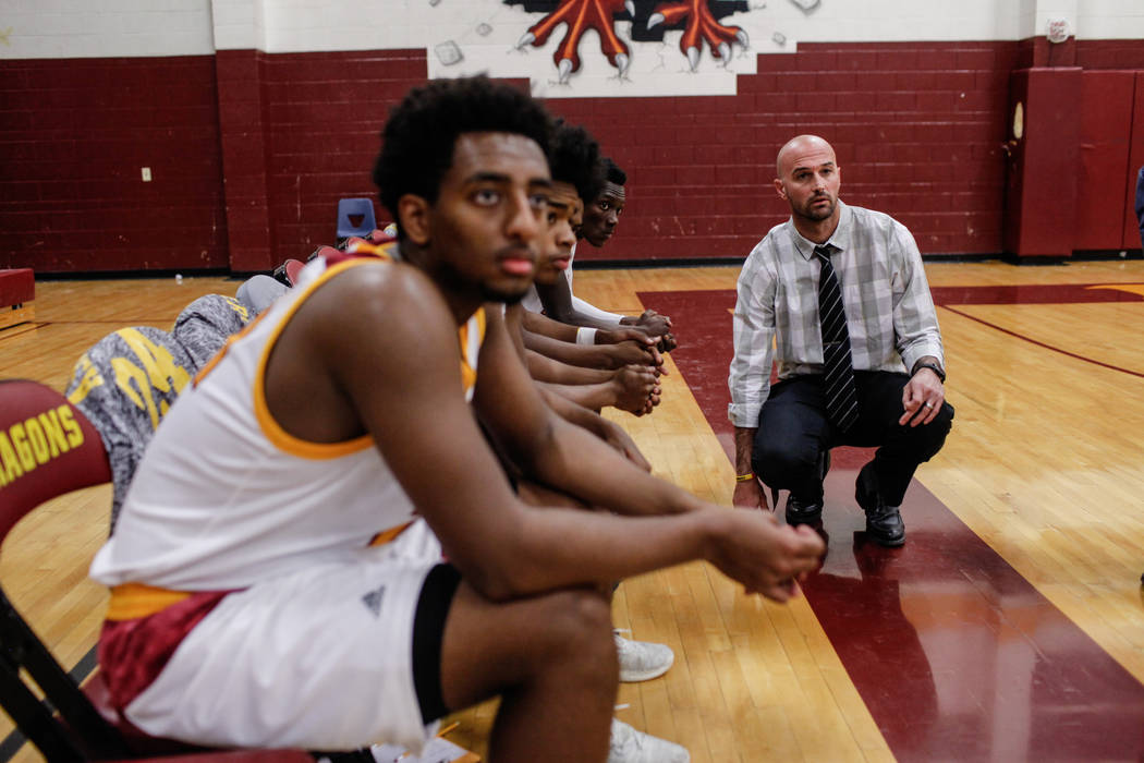 Del Sol head coach Tyler Ehrke kneels next to his players before the start of the first quarter of a basketball game against Southeast Career Tech at Del Sol High School in Las Vegas, Thursday, De ...