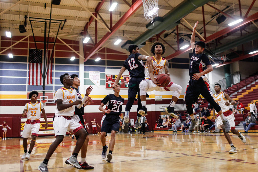 Del Sol's Devonte Anton Villarta (10) shoots the ball as he is guarded by Southeast Career Tech's Manny Board (12) and Jurelle Orbino (1) during the second quarter of a basketball game at Del Sol  ...