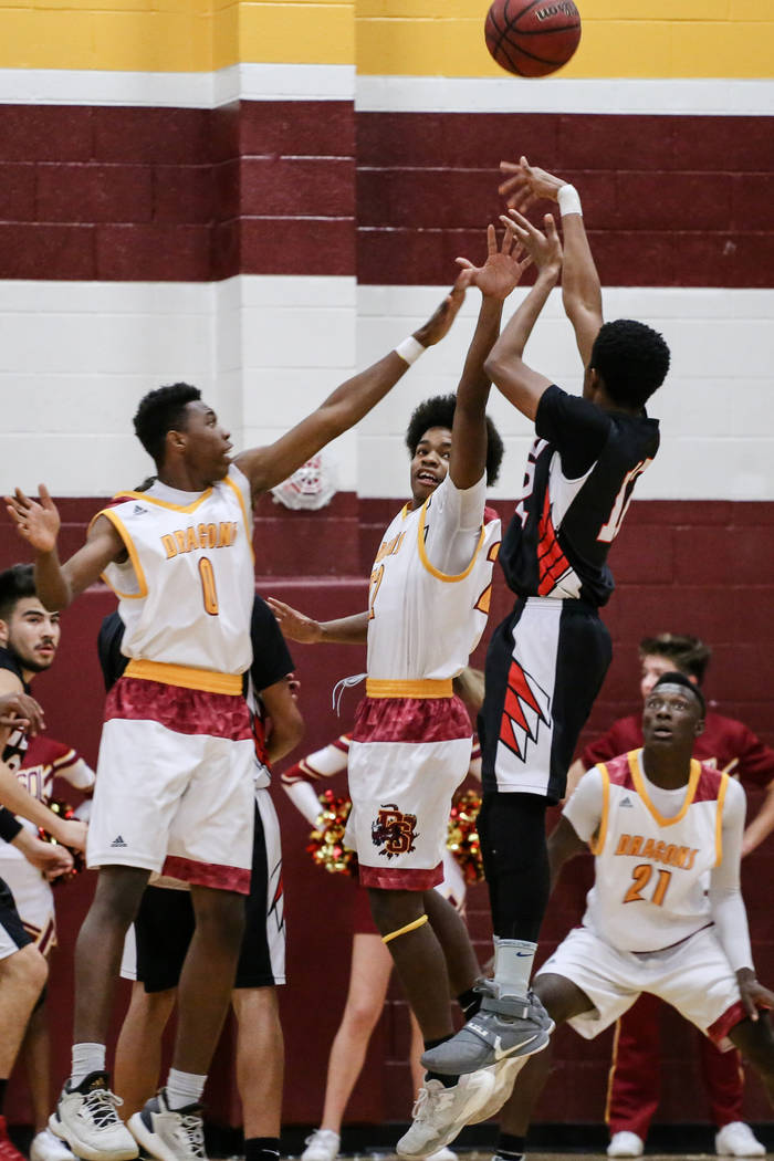 Del Sol's Tyrell Hampton (0) and Keith Seldon (22) block Southeast Career Tech's Manny Board (12) during the first quarter of a basketball game at Del Sol High School in Las Vegas, Thursday, Dec.  ...