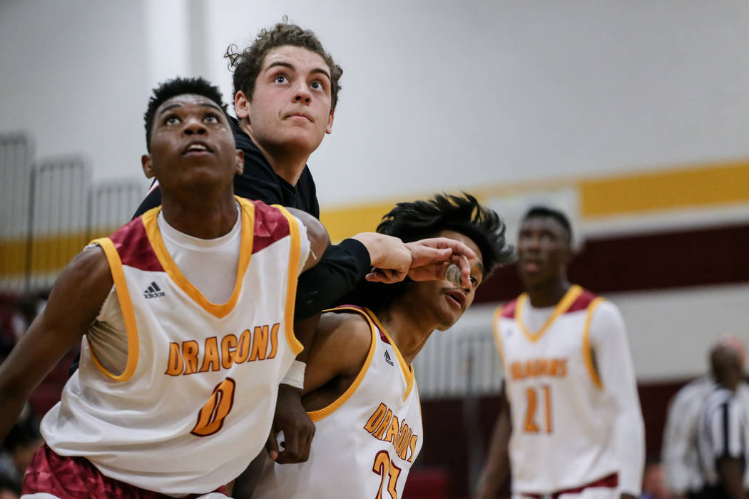 Del Sol's Tyrell Hampton (0), Denson Tablidillo (23) and Southeast Career Tech's Ryan Fisher (22) react after a free-throw during the third quarter of a basketball game at Del Sol High School in L ...