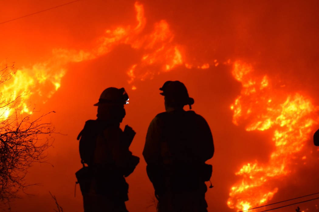 Santa Barbara County Fire Department firefighters knock down flames as they advance on homes atop Shepherd Mesa Road in Carpinteria, Calif., Sunday, Dec. 10, 2017. A flare-up on the western edge o ...
