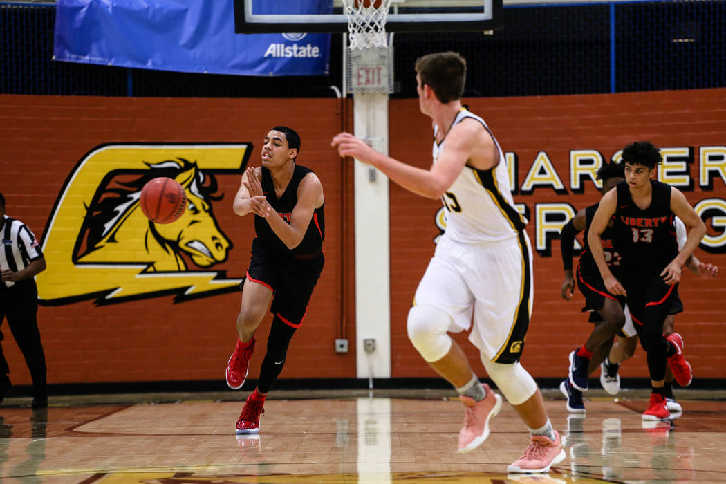 Liberty's Julian Strawther (0), left, shoots passes the ball during the first quarter of a basketball game against the Clark Chargers at Ed W. Clark High School in Las Vegas, Friday, Dec. 15, 2017 ...