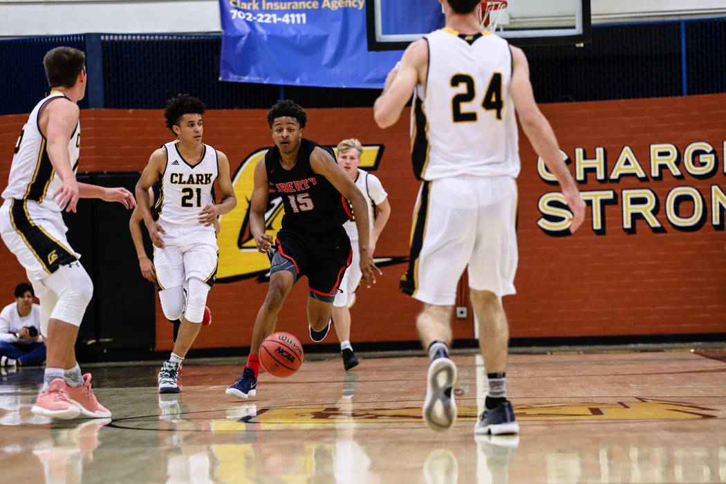 Clark Chargers' Jalen Hill (21) and Libertyͳ Cameron Burist (15) chase after the ball during the first quarter of a basketball game at Ed W. Clark High School in Las Vegas, Friday, Dec. 15,  ...