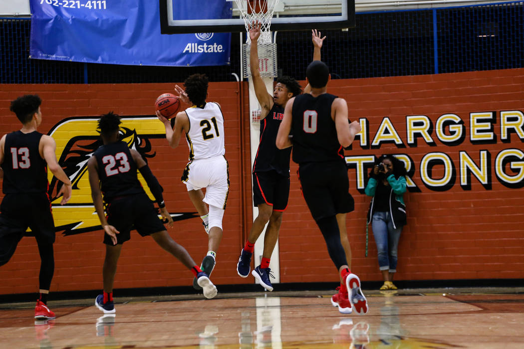 Clark Chargers' Jalen Hill (21) shoots the ball as Libertyͳ Cameron Burist (15) attempts to block him during the first quarter of a basketball game at Ed W. Clark High School in Las Vegas, F ...