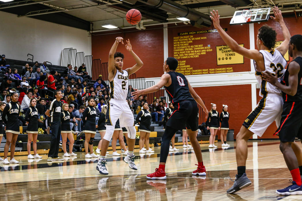 Clark Chargers' Jalen Hill (21) passes the ball as he is guarded by Liberty's Julian Strawther (0) during the second quarter of a basketball game at Ed W. Clark High School in Las Vegas, Friday, D ...