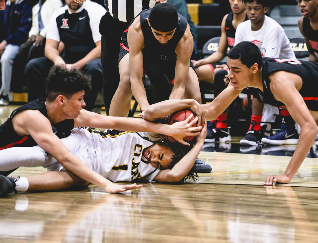Clark Chargers' Frankie Collins (1) holds onto the ball as players from Liberty attempt to steal it during the third quarter of a basketball game at Ed W. Clark High School in Las Vegas, Friday, D ...