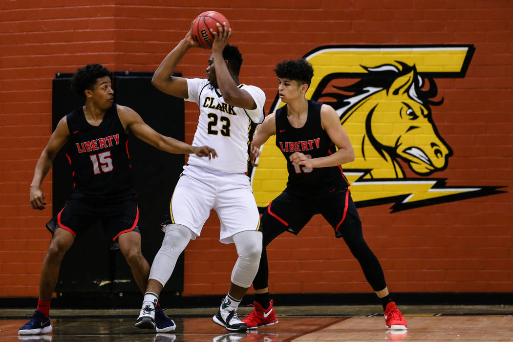 Liberyճ Cameron Burist (15) and teammate Liberyճ Terrance Marigney (13) guard Clark ChargersՠAntwon Jackson (23) during the first quarter of a basketball game at Ed W. Clark High ...