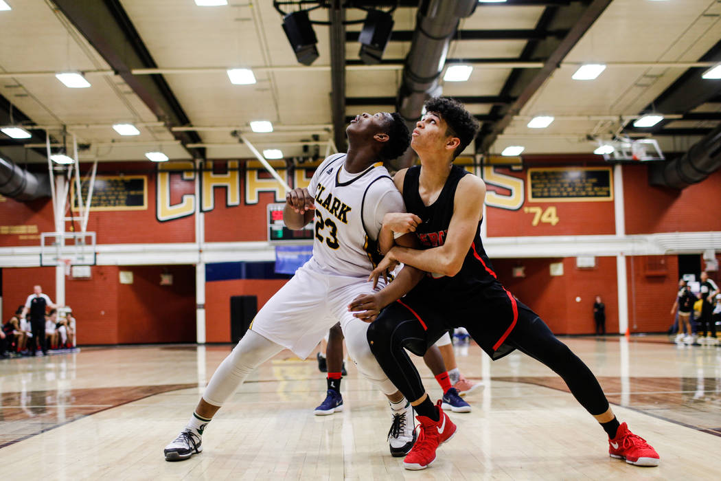 Clark ChargersՠAntwon Jackson (23) and Liberyճ Terrance Marigney (13) look up for a rebound during the fourth quarter of a basketball game at Ed W. Clark High School in Las Vegas, Frid ...