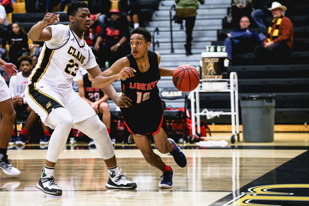 Clark ChargersՠAntwon Jackson (23) guards Liberyճ Jordan Holt (10) during the third quarter of a basketball game at Ed W. Clark High School in Las Vegas, Friday, Dec. 15, 2017. Clark C ...