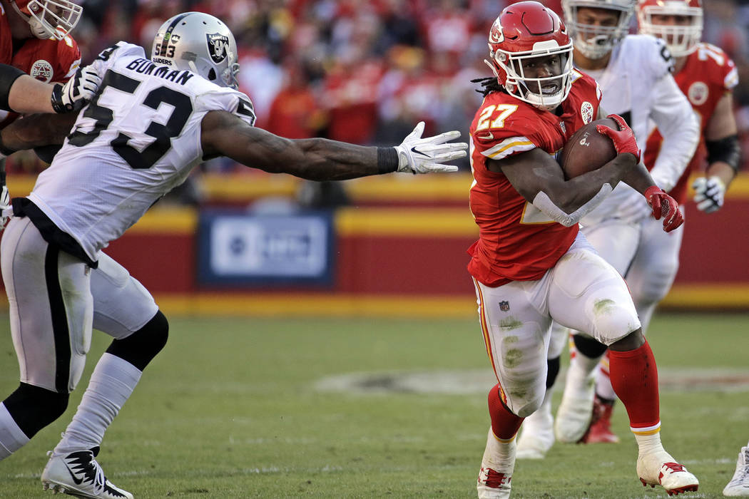 Kansas City Chiefs running back Kareem Hunt (27) carries the ball away from Oakland Raiders linebacker NaVorro Bowman (53) during the second half of an NFL football game in Kansas City, Mo., Sunda ...