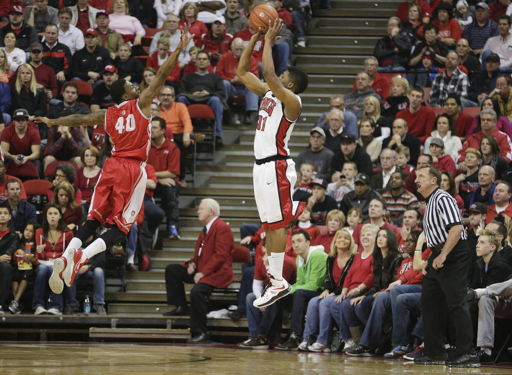 UNLV's Justin Hawkins (31) shoots over New Mexico's Demetrius Walker in the first half of an NCAA college basketball game, Saturday, Feb. 9, 2013, in Las Vegas. (AP Photo/Julie Jacobson)