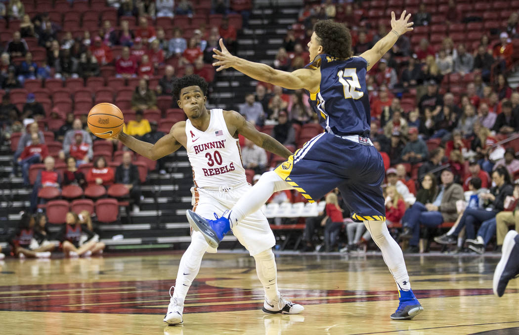 UNLV Rebels guard Jovan Mooring (30) passes the ball past Northern Colorado Bears guard Jonah Radebaugh (12) during the second period of an NCAA college basketball game at the Thomas & Mack Ce ...