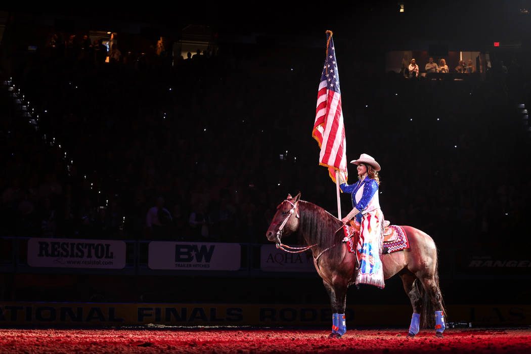 A rider holds the American flag during the national anthem at the start of the fifth night of the 59th Wrangler National Finals Rodeo at the Thomas & Mack Center in Las Vegas, Monday, Dec. 11, ...