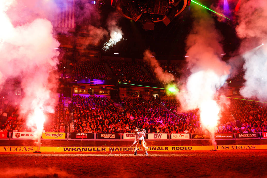 A performer is surrounded by fireworks during start of the fifth night of the 59th Wrangler National Finals Rodeo at the Thomas & Mack Center in Las Vegas, Monday, Dec. 11, 2017. Joel Angel Ju ...