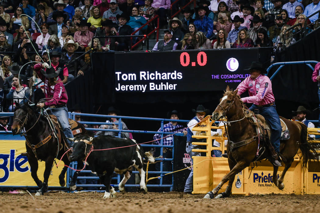 Jeremy Buhler of Arrowwood, Alberta, left, and Tom Richards of Humboldt, Ariz., right, chase down a steer in the team roping event during the fifth night of the 59th Wrangler National Finals Rodeo ...