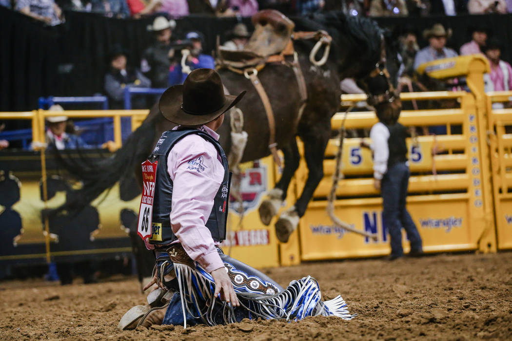 Jake Wright of Milford, Utah kneels after being bucked off of Double D in the saddle bronc riding event during the fifth night of the 59th Wrangler National Finals Rodeo at the Thomas & Mack C ...