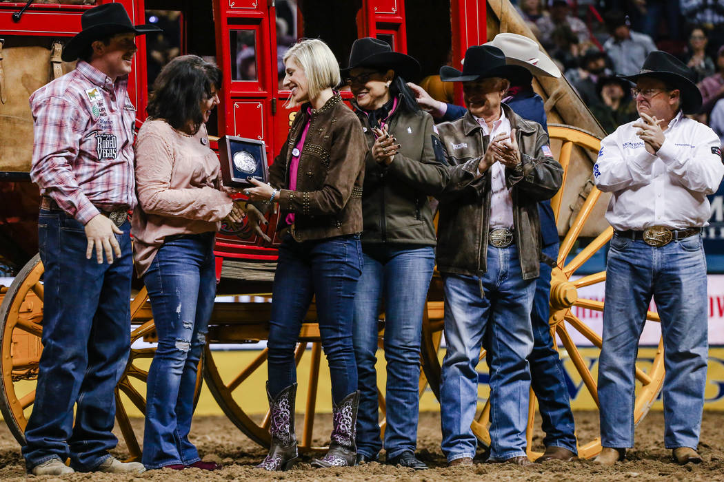 Nick Guy of Sparta, Wis., left, stands next to his mother Diane Matousek, second from left, as she is presented an award during the fifth night of the 59th Wrangler National Finals Rodeo at the Th ...