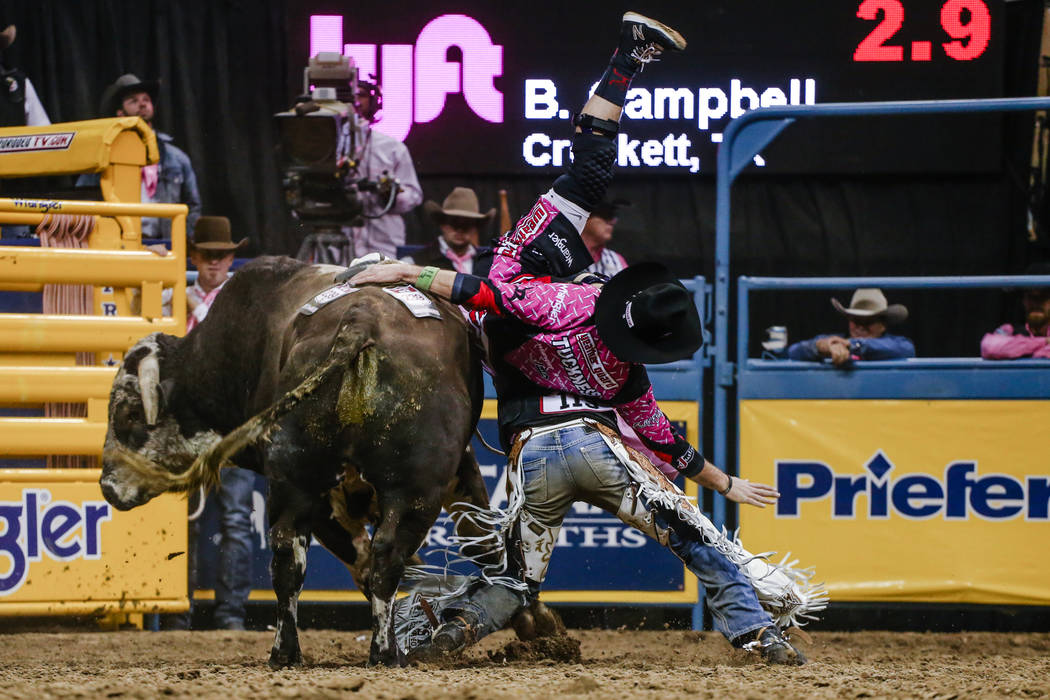 Red Bandana knocks off Boudreaux Campbell of Crockett, Texas, bottom right, as he collides with a bullfighter, top right, in the bull riding event during the fifth night of the 59th Wrangler Natio ...