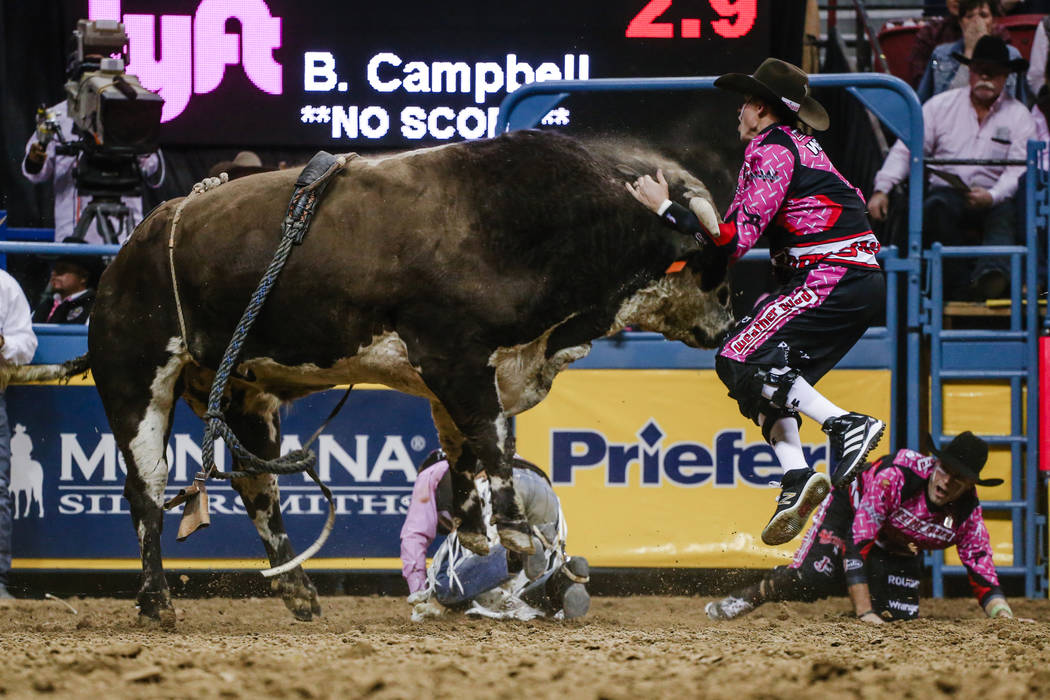 Red Bandana hits a bullfighter after knocking off Boudreaux Campbell of Crockett, Texas in the bull riding event during the fifth night of the 59th Wrangler National Finals Rodeo at the Thomas &am ...