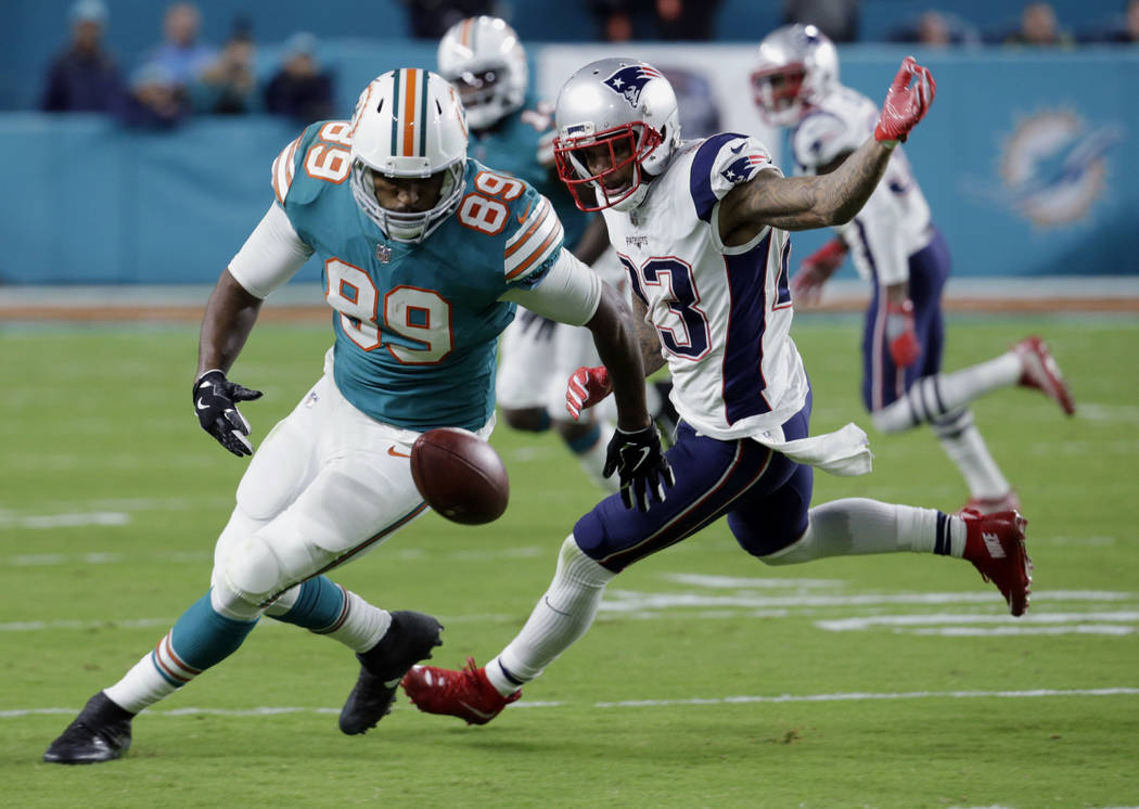 Miami Dolphins tight end Julius Thomas (89) drops a pass but recovers it as New England Patriots strong safety Patrick Chung (23) defends, during the first half of an NFL football game, Monday, De ...
