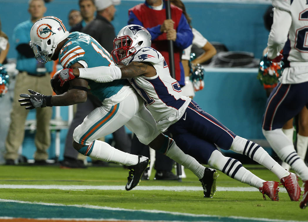 Miami Dolphins wide receiver Jarvis Landry (14) runs for a touchdown as New England Patriots cornerback Jonathan Jones (31) attempts to tackle, during the first half of an NFL football game, Monda ...