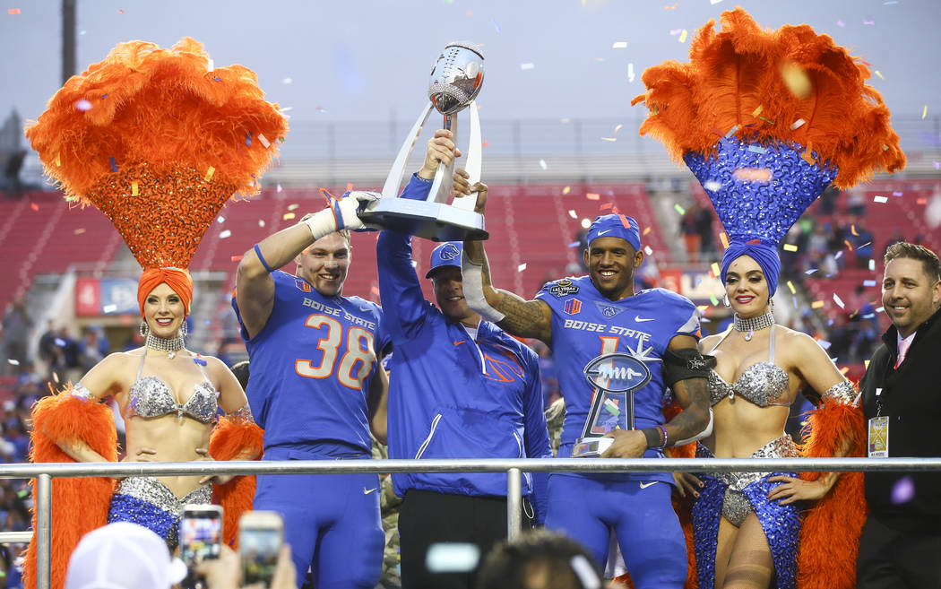 Boise State head coach Bryan Harsin, center, celebrates with players Leighton Vander Esch, left, and Cedrick Wilson after defeating Oregon in the Las Vegas Bowl at Sam Boyd Stadium in Las Vegas on ...