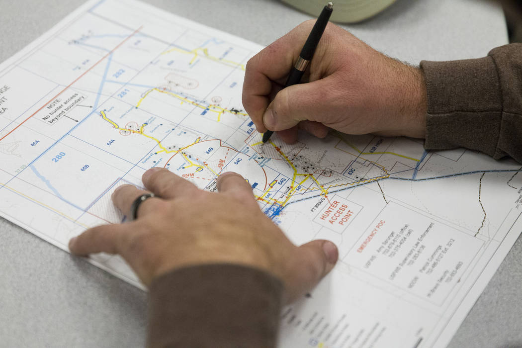Patrick White of Reno makes a note in his map during an orientation at the Clark County Shooting Complex for hunters randomly picked for the annual bighorn sheep hunt inside the Nevada Test and Tr ...