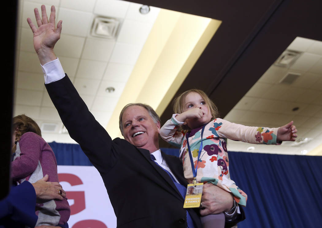 Doug Jones waves to supporters before speaking during an election-night watch party Tuesday, Dec. 12, 2017, in Birmingham, Ala. Jones won election to the U.S. Senate from Alabama, dealing a politi ...